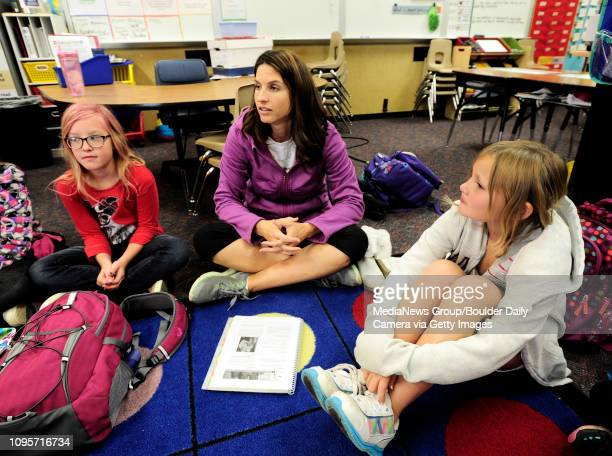Lily Pate, left and Madeline Smith listen to teacher Mishel Reilly, center, talk about positive body image during a Girls on the Run of the Rockies...
