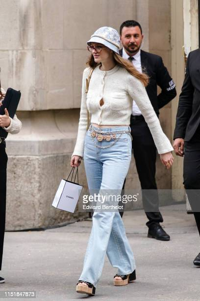 Lily Taieb wears a light blue hat a white Chanel jacket a Chanel necklace blue jeans black Chanel sandals with cork platform outside the Chanel...