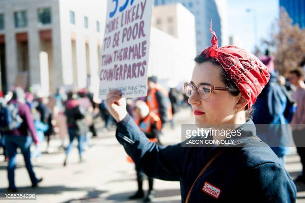 Lily Williams of Denver Colorado dressed as Rosie the Riveter holds up a sign as demonstrators march past her during during the Women's March in...