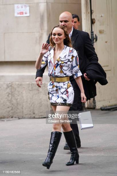 LilyRose Depp wears a Chanel colorful mini dress a golden Chanel belt black boots outside the Chanel Cruise Collection 2020 At Grand Palais on May 03...