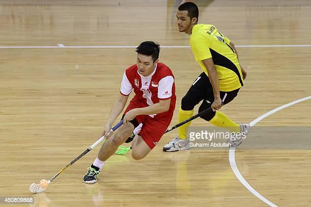 Lim Hanrong Calvin of Singapore dribbles past Mohd Haidar Takiyudin of Malaysia during the World University Championship Floorball match between...