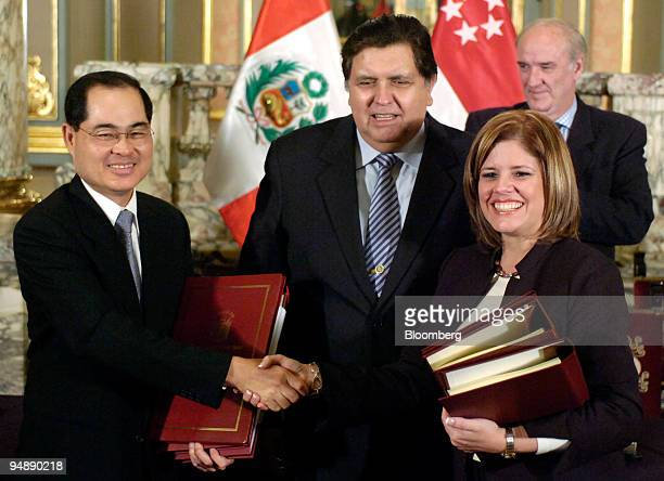 Lim Hng Kiang Singapore's minister for trade and industry left and Mercedes Araoz Peru's minister for international trade shake hands as Alan Garcia...
