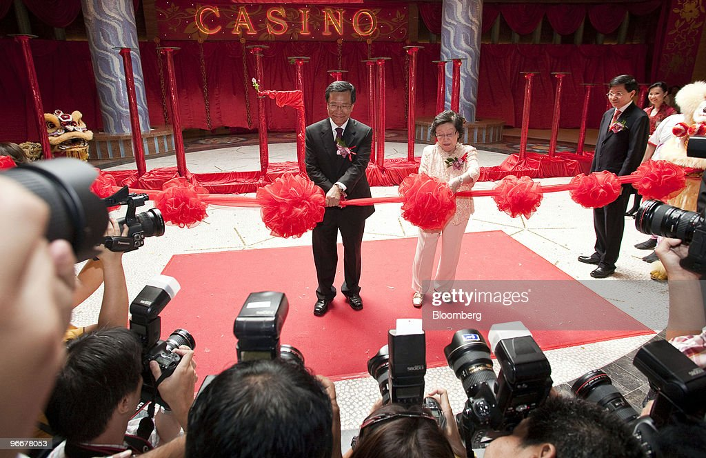 Lim Kok Thay, chairman and chief executive officer of Genting Bhd., left, cuts the ribbon with his mother, Lee Kim Hua, during the ceremony marking the soft opening of Genting Singapore Plc's Resorts World Sentosa casino in Singapore, on Sunday, Feb. 14, 2010. Genting Singapore Plc, the unit of Asia's largest publicly traded gambling operator, opened the country's first casino as Lunar New Year celebrations commenced. Photographer: Charles Pertwee/Bloomberg via Getty Images