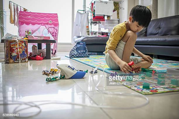 Lim Seongjoon who is suffering from chronic lung disease plays a game by himself as he is connected to an oxygen tank at home on May 6 2016 in Yongin...