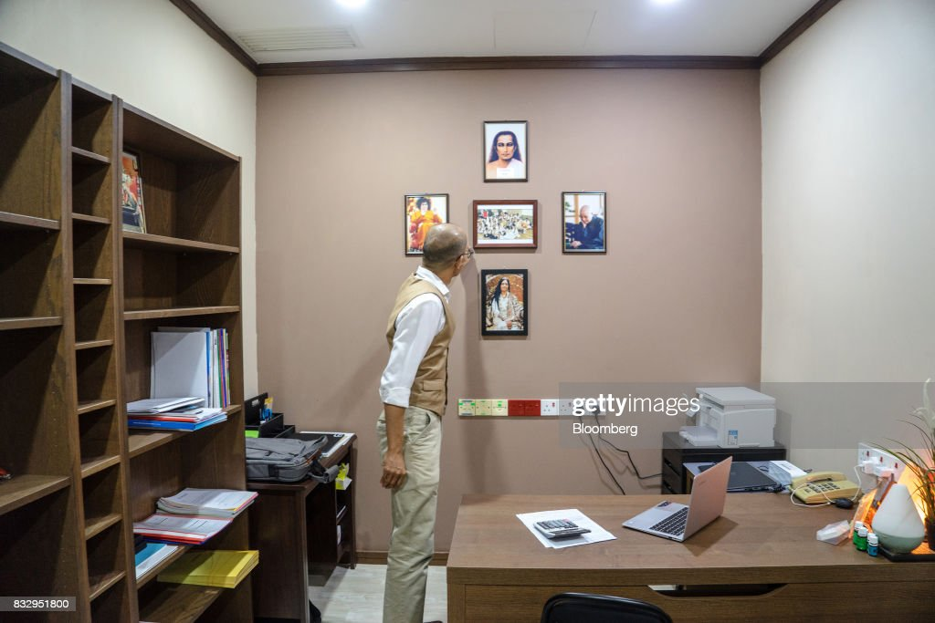 Lim Tze Cheng, chief executive officer of Inter-Pacific Asset Management Sdn., aligns pictures of his religious gurus on his office wall in Kuala Lumpur, Malaysia, on Tuesday, Aug. 15, 2017. Lim has been buying Malaysian technology and manufacturing stocks that he thinks will increase profit over the long term, betting that the rally in technology has several years to run. Photographer: Sanjit Das/Bloomberg via Getty Images