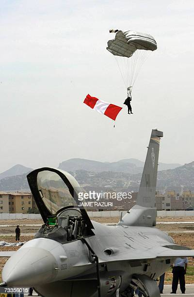A Peruvian Air Force paratrooper descends behind a US Air Force F16 jet fighter aircraft at Las Palmas Peruvian Air Force Base in Lima on February...