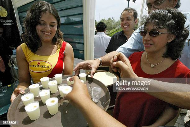 A waitress offers 'pisco sour' during a public toast as part of the celebrations of the Pisco Sour's National Day 03 February 2006 in Lima Pisco is...