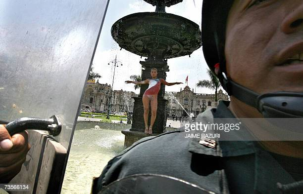 Peruvian model Reina Loo poses almost naked with the Chilean flag painted on her body in the fountain of the Plaza Mayor in Lima 13 March 2007 as a...