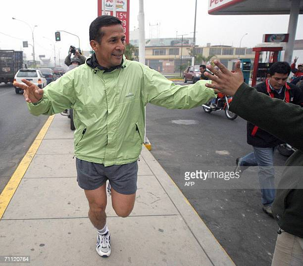 The Peruvian presidential candidate Ollanta Humala of the Union for Peru party is greeted by a supporter during an early jog near his home before...