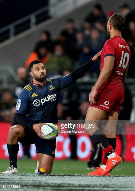 Lima Sopoaga of the Highlanders is appraoched by Quade Cooper of the Reds as he lines up a conversion during the round 17 Super Rugby match between...