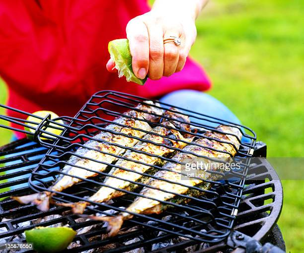 lime being squeezed over mackerel on barbecue - mackerel stock pictures, royalty-free photos & images