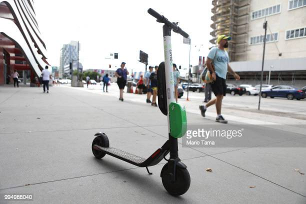 Lime dockless electric scooter is parked on a Wilshire Boulevard sidewalk available for its next rider on July 9 2018 in Los Angeles California Uber...