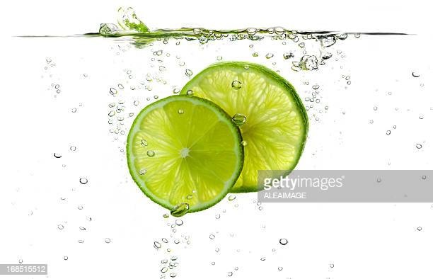 Lime slices splashing in fresh water
