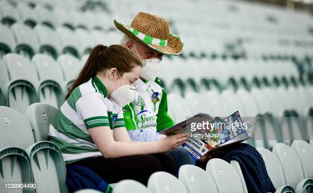 Limerick , Ireland - 10 July 2021; Isabelle Hurley, aged 11, from Castlemahon, Limerick, reads the match programme with her grandfather Patrick...