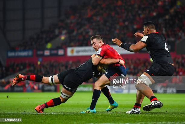 Limerick Ireland 7 December 2019 JJ Hanrahan of Munster is tackled by Ben Earl left and Will Skelton of Saracens during the Heineken Champions Cup...