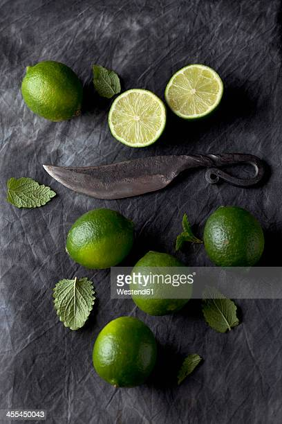 Limes with leaves and knife on black textile, close up