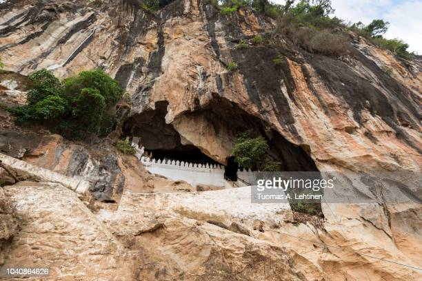 limestone cliff and entrance to the famous pak ou caves near luang prabang in laos, viewed from the front. - formación karst fotografías e imágenes de stock