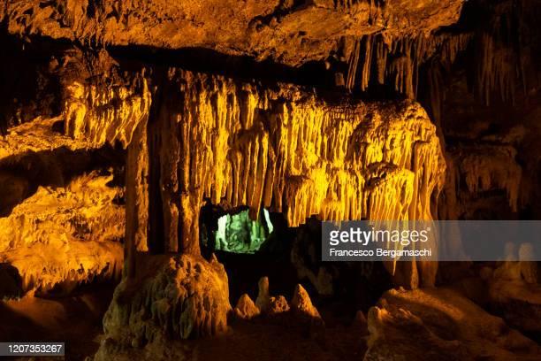 limestone concretions(stalactites and stalagmites) illuminated by artificial lights. - italia stockfoto's en -beelden