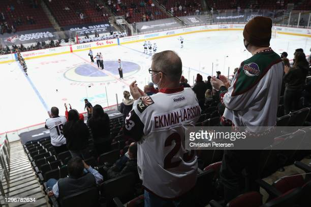 Limited attendance fans, stand and cheer after the notional anthem to NHL game between the Arizona Coyotes and the San Jose Sharks at Gila River...