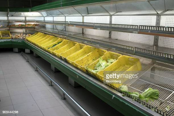Limited supplies of vegetables sit on near empty shelves at a grocery store in Caracas Venezuela on Tuesday Jan 9 2018 Hordes of desperate shoppers...