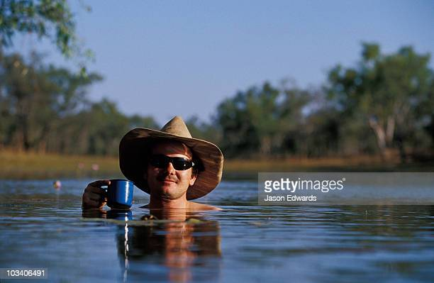 A National Park ranger cools off with a drink in an outback billabong.