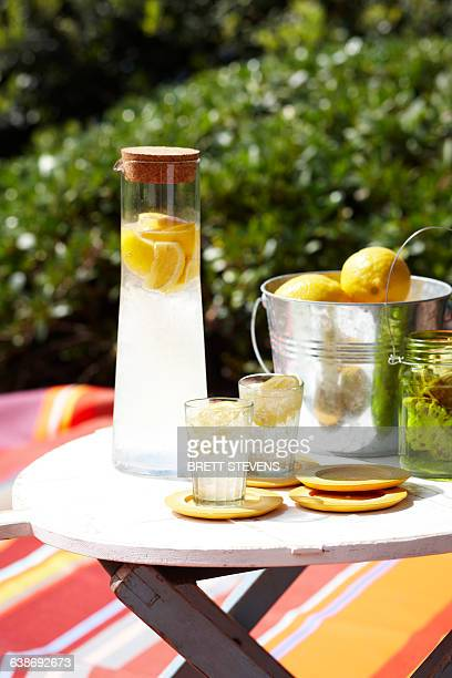 Limoncello soda in glass carafe and ice bucket of lemons on table