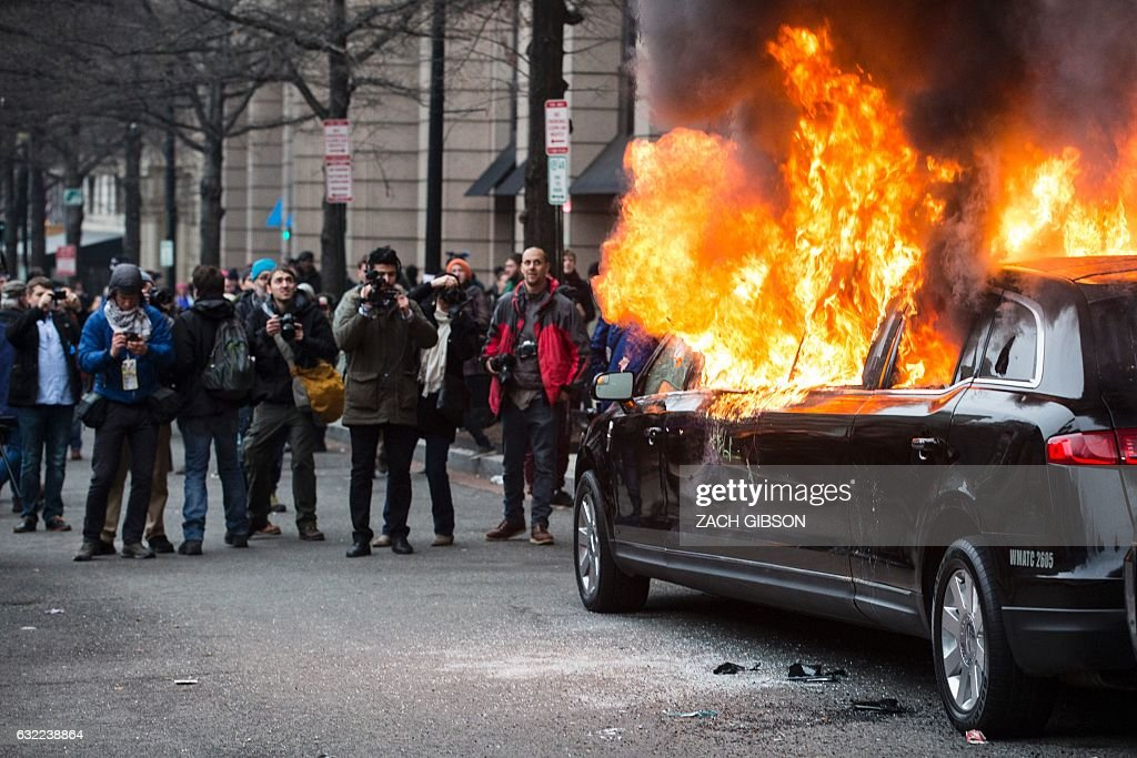 TOPSHOT - A limousine burns during a protest reacting to the inauguration of US President Donald Trump on January 20, 2017 in Washington, DC. / AFP / ZACH