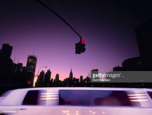 Limousine car passing junction in Midtown Manhattan at sunrise