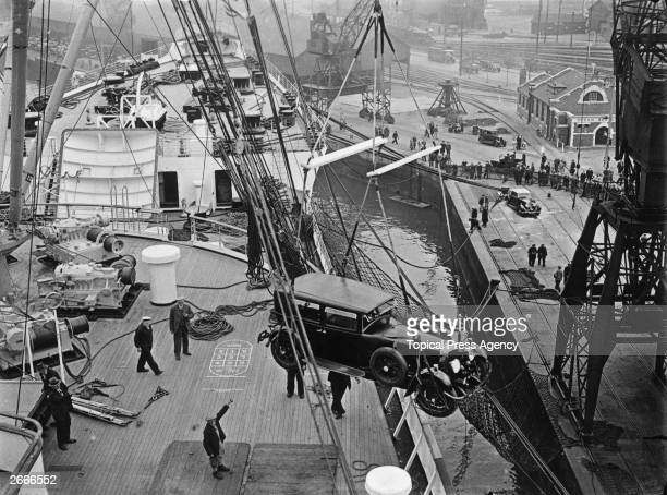 A limousine is hoisted onto the deck of the new Cunard White Star liner Queen Mary hours before her departure on her maiden voyage from Southampton...