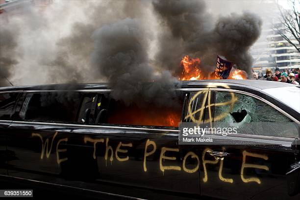 A limousine is set aflame with the graffiti of 'We the People' spray painted on the side after the inauguration of Donald Trump as the 45th President...