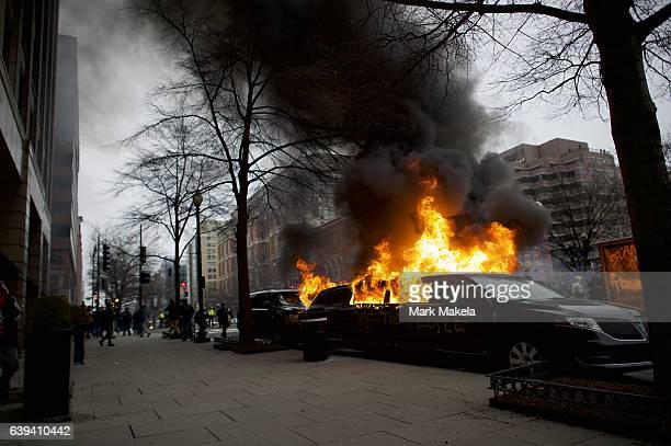 A limousine is set aflame with 'We the People' spray painted on the side after the inauguration of Donald Trump as the 45th President of the United...