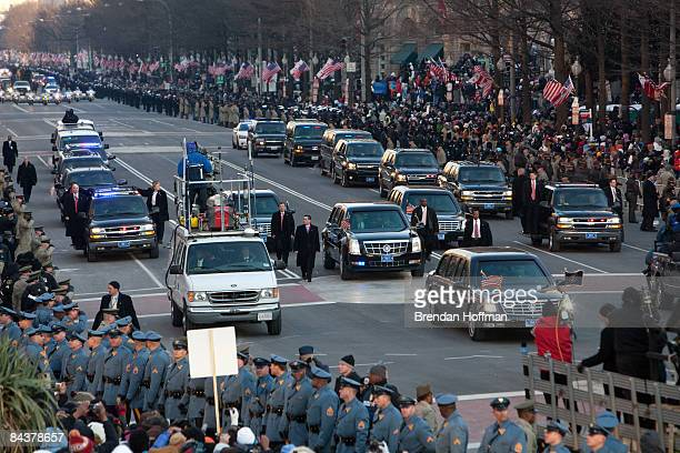 A limousine surrounded by four Secret Service agents carries President Barack Obama during the Inaugural Parade down Pennsylvania Avenue on January...
