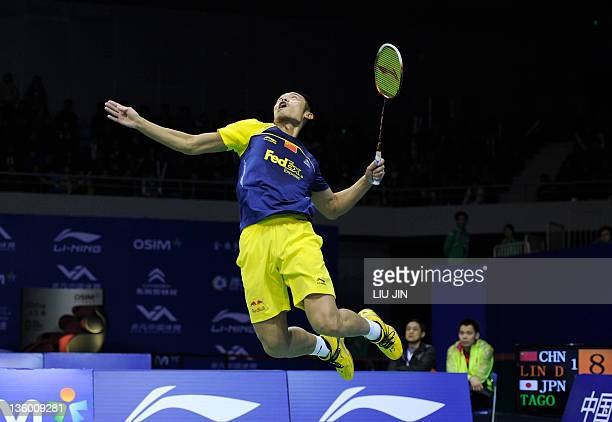 Lin Dan of China leaps to smash a shuttlecock against Kenichi Tago of Japan during their men's singles Group B match of BWF badminton World...