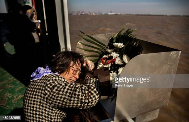 Lin Hui Zhen 76 years weeps as she clutches the small bag carrying the ashes of her late husband Fu Yao Ming 80 years before placing them in a metal...