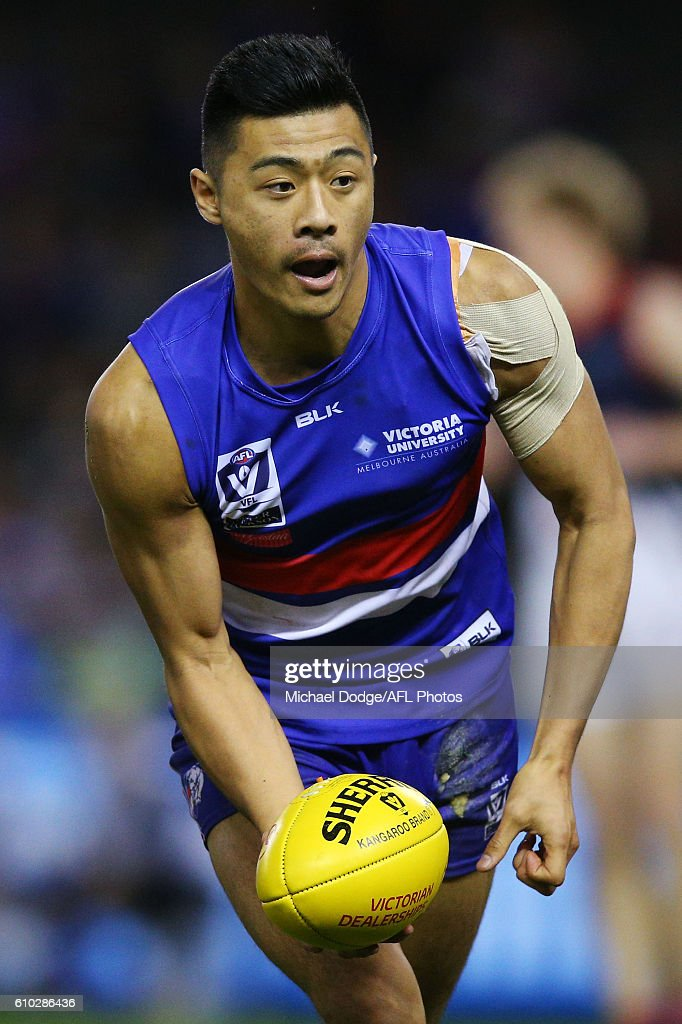 Lin Jong of Footscray, wearing tape on his non-injured shoulder for disguise, handballs during the VFL Grand Final match between the Casey Scorpions and the Footscray Bulldogs at Etihad Stadium on September 25, 2016 in Melbourne, Australia.