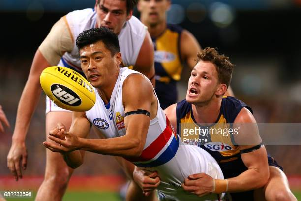 Lin Jong of the Bulldogs gets his handball away while being tackled by Jack Redden of the Eagles during the round eight AFL match between the West...