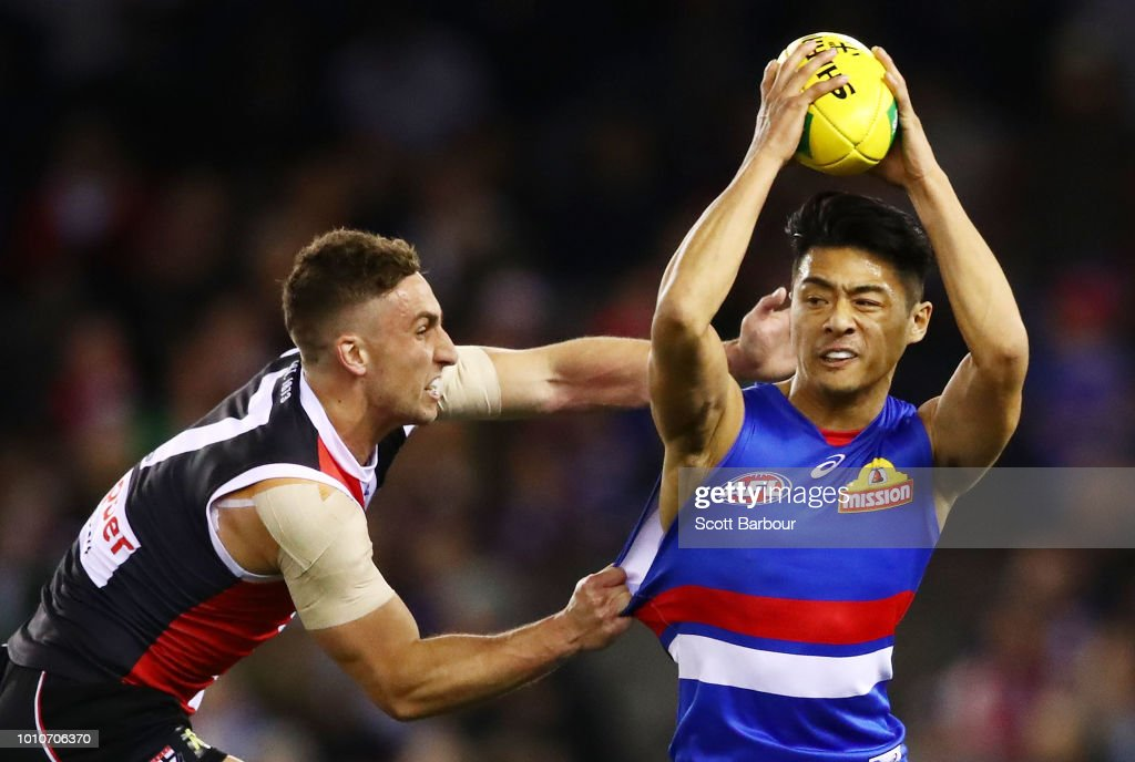 Lin Jong of the Bulldogs is tackled by Luke Dunstan of the Saints during the round 20 AFL match between the St Kilda Saints and the Western Bulldogs at Etihad Stadium on August 4, 2018 in Melbourne, Australia.