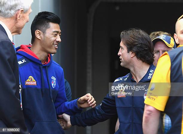 Lin Jong of the Bulldogs wishes Luke Beveridge good luck during the 2016 AFL Grand Final match between the Sydney Swans and the Western Bulldogs at...
