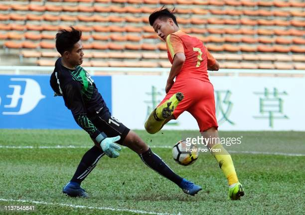 Lin Liangming of China attempts to dribble past Xaysavath of Laos during the AFC U23 Championship qualifier between China and Laos at Shah Alam...