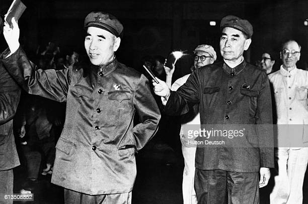 Lin Piao and the Prime Minister Chou En Lai wave their little red books containing the quotations of Chairman Mao at a 1967 celebration of his...