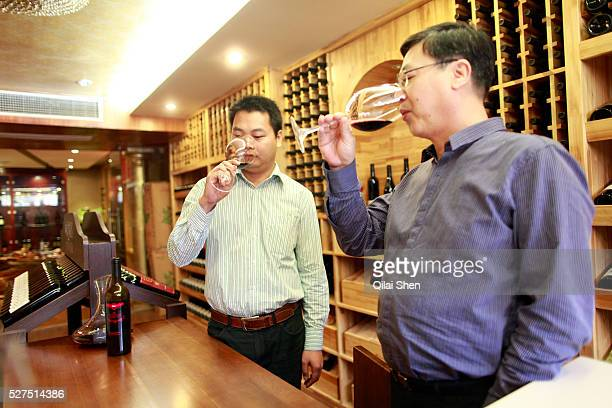 Lin Tiangui a representative of Winston Wine shares a glass of wine with Huang Yongqiang a store manger at one of its stores in Shanghai China on 18...