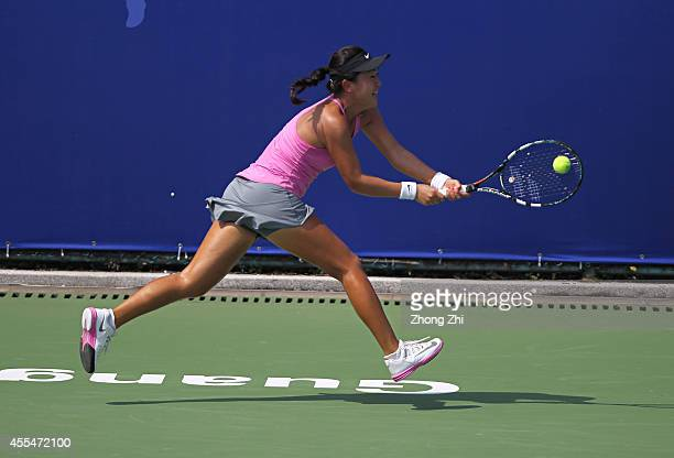 Lin Zhu of China returns a shot during her match against Roberta Vinci of Italy during day one of the 2014 WTA Guangzhou Open at Taint Sports Center...