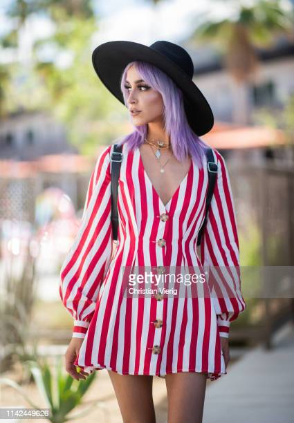 Lina Assayed is seen wearing red striped dress, black hat, backpack on April 12, 2019 in Indio, California.