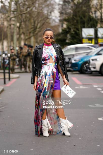 """Lina Lindholm """"Lina x Muse"""" wears sunglasses, a black leather jacket, a silver shiny dress with a keyhole and multicolor floral print, a purple..."""