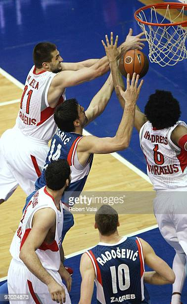 Linas Kleiza #11 and Josh Childress #6 of Olympiacos Piraeus competes with Dalibor Bagaric #14 of Cibona in action during the Euroleague Basketball...