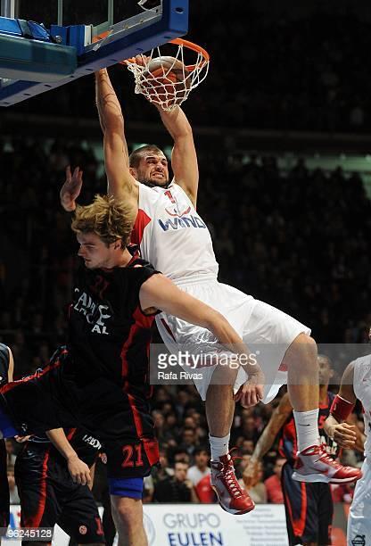 Linas Kleiza #11 of Olympiacos Piraeus scores next to Tiago Splitter #21 of Caja Laboral during the Euroleague Basketball 20092010 Last 16 Game 1...