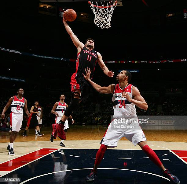Linas Kleiza of the Toronto Raptors dunks against JaVale McGee of the Washington Wizards during the game at the Verizon Center on February 6 2012 in...