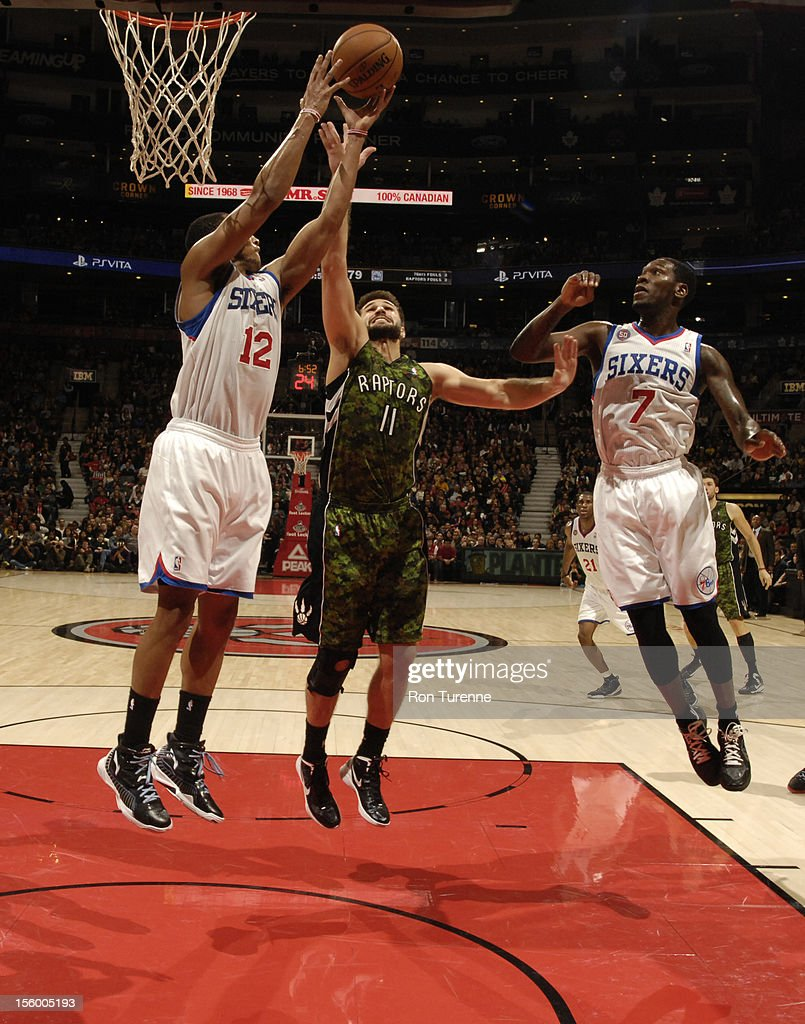 Linas Kleiza #11 of the Toronto Raptors fights for a rebound against Evan Turner #12 and Royal Ivey #7 of the Philadelphia 76ers during the game on November 10, 2012 at the Air Canada Centre in Toronto, Ontario, Canada.