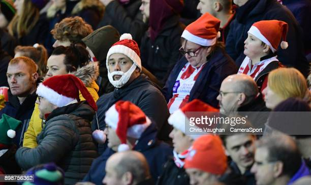 Lincoln City fans in festive attire watch their team in action during the Sky Bet League Two match between Lincoln City and Stevenage at Sincil Bank...