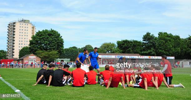 Lincoln City manager Danny Cowley and Lincoln City's assistant manager Nicky Cowley deliver their prematch team talk to their players on the pitch...